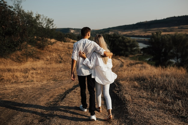 キャンプ旅行で愛するカップルが郡道を歩いています。