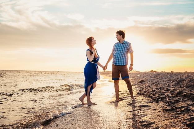 Влюбленная пара на берегу моря на закате