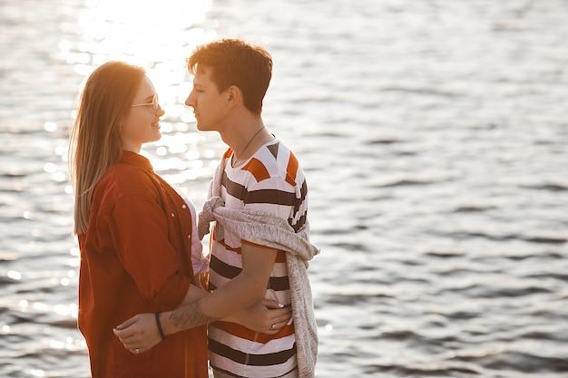 サンセットビーチで愛するカップル。女性と男性が一緒に