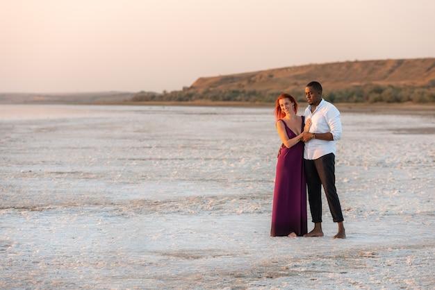 日没時の休暇で愛するカップル。幸せな混血ミレニアル世代のカップル。日没時の新婚旅行