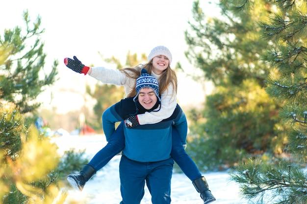 사랑의 부부는 숲에서 겨울에 재생합니다. 여자는 크리스마스 트리 배경에서 남자를 탄다. 웃으면 서 즐거운 시간 보내세요
