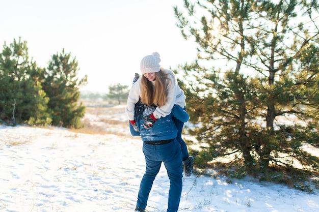 사랑의 부부는 숲에서 겨울에 재생합니다. 그 남자는 여자를 등 뒤로 던지고 숲을 통해 그녀와 함께 뛰었습니다. 웃으면 서 즐거운 시간을 보내십시오.