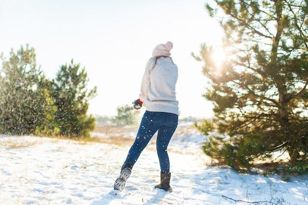 사랑의 부부는 숲에서 겨울에 눈덩이를 재생합니다. 서로 눈을 던져. 웃으면 서 즐거운 시간 보내세요