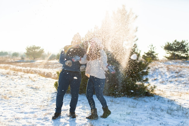 Loving couple play snowballs in winter in the forest. throw each other snow. laugh and have a good time