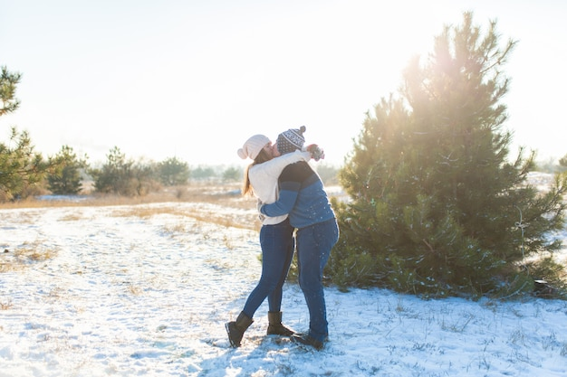 Loving couple play snowballs in winter in the forest.