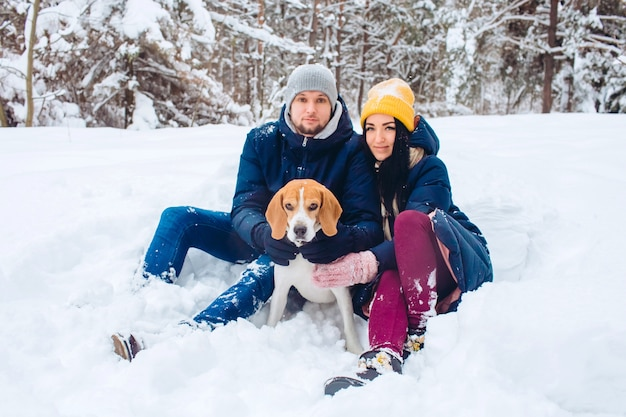 Loving couple playing with snow in cold weather,  active winter holiday with beagle dog.