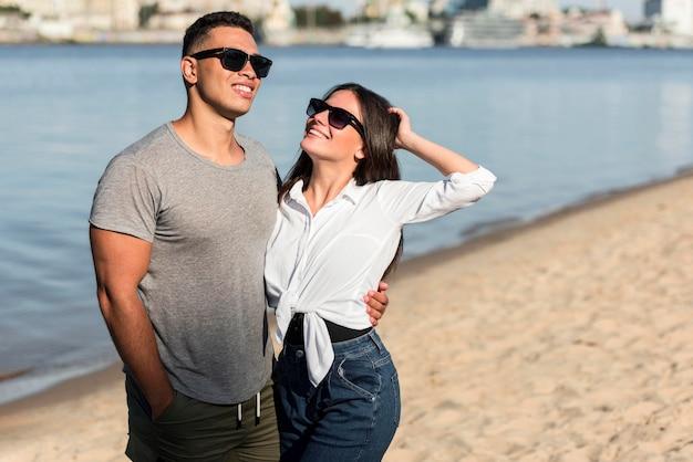 ビーチで一緒にポーズをとって愛するカップル
