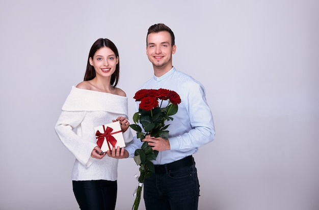Loving couple posing with a gift and red roses, smiling.