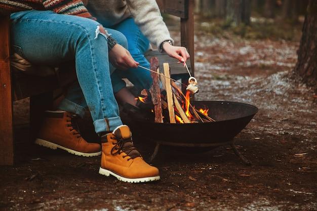 愛するカップルが火のそばでマシュマロを準備します。秋の森、ロマンチックな日。セレクティブフォーカス