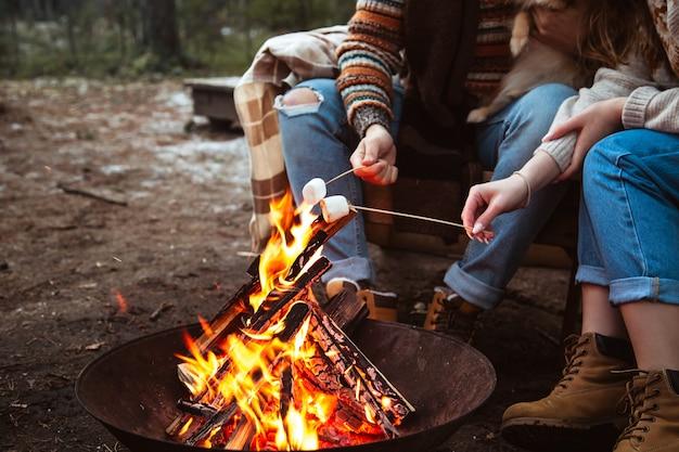 愛するカップルが火のそばでマシュマロを準備します。秋の森、