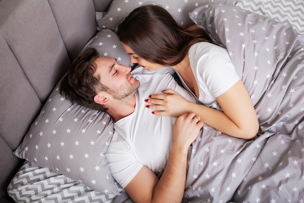 Loving couple relaxing in bed at home