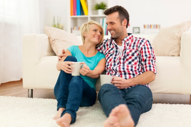 Loving couple relaxing at home with cup of coffee