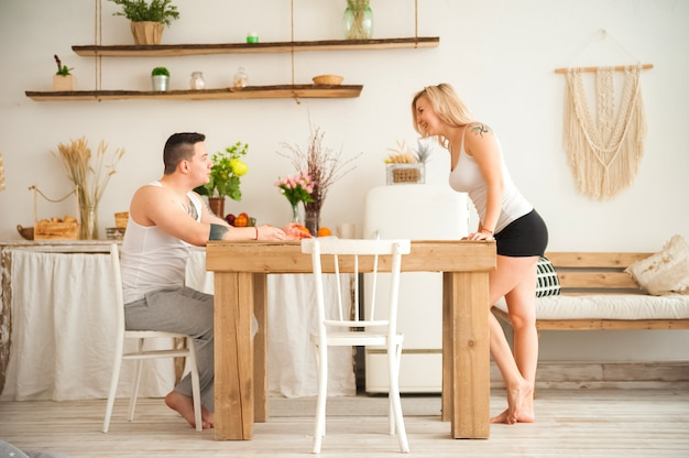 Loving couple in a rustic kitchen and copy space. loving couple with tattoos in a scandinavian style kitchen.