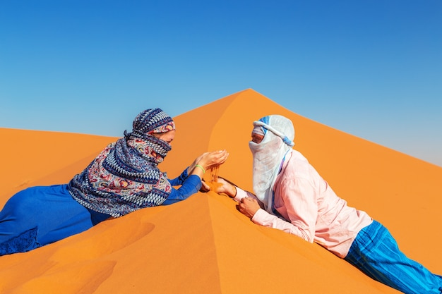 Loving couple in the sahara desert. joint rest.