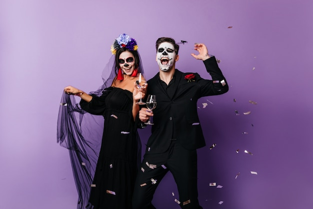 Loving couple in scary attire celebrating day of the dead. joyful girl and boy dancing at halloween party.