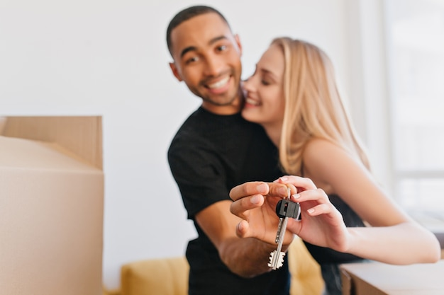 Loving couple showing keys of new house, going to move to new apartment, bought flat, packing cardboard boxes, relocating.