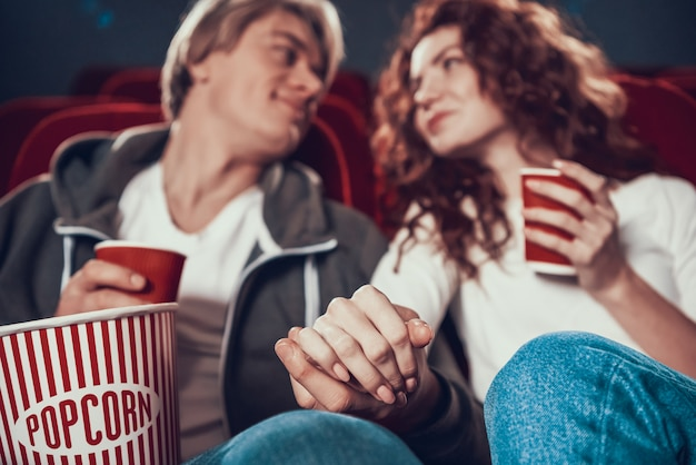 Loving couple sit holding hands in cinema.