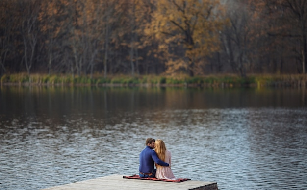 Loving couple sits in an embrace on the pier by the lake with a beautiful view
