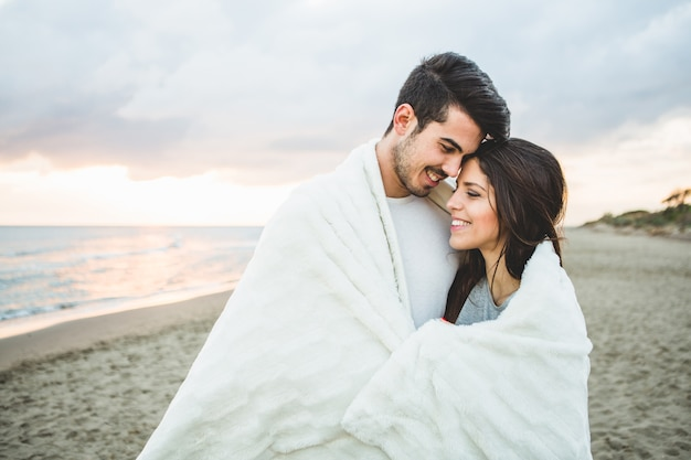 Loving couple sitting on a beach covered by a white blanket