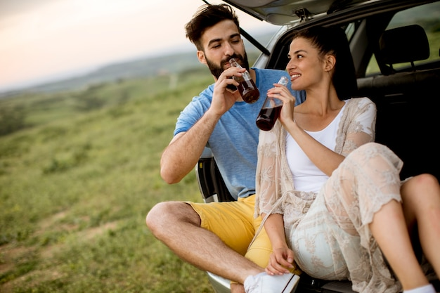 Loving couple sitting in the car trank during trip in the nature