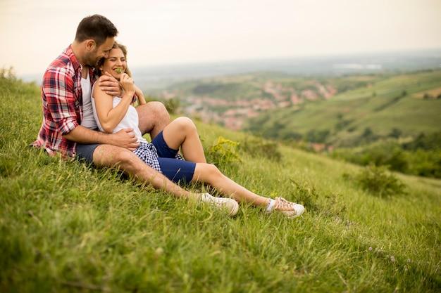 愛情のあるカップルの座っている山の芝生の上で抱きしめ