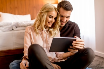 Loving couple sitting on the floor in bedroom and using digital tablet