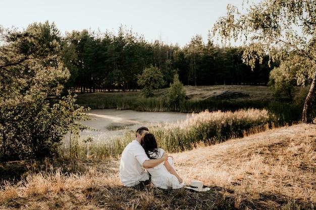 Влюбленная пара, сидя на траве на закате летом. брюнетка девушка в легком платье. история о любви.