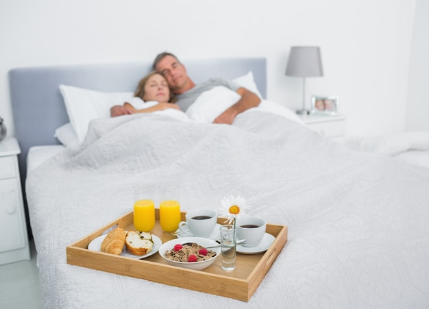 Loving couple sleeping with breakfast tray on bed