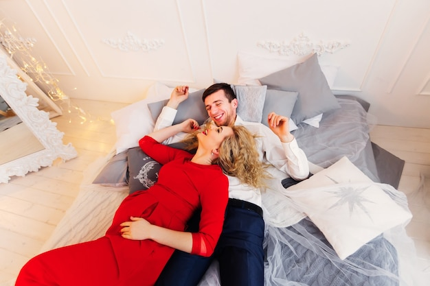 Loving couple smiles on the bed with a lot of pillows