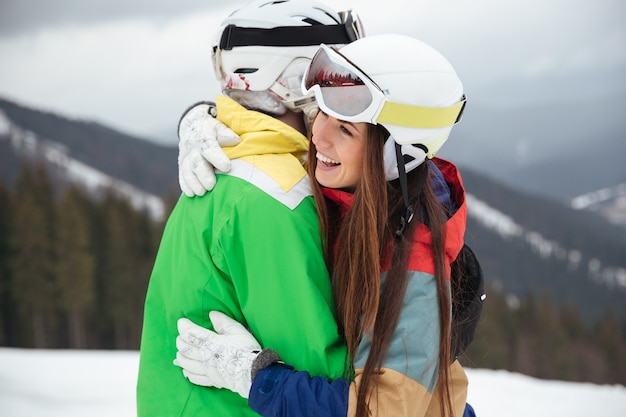 Loving couple snowboarders on the slopes frosty winter day hugging