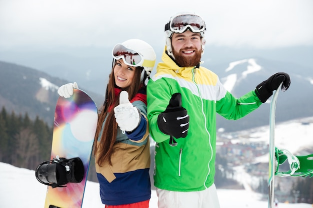 Loving couple snowboarders on the slopes frosty winter day making thumbs up gesture