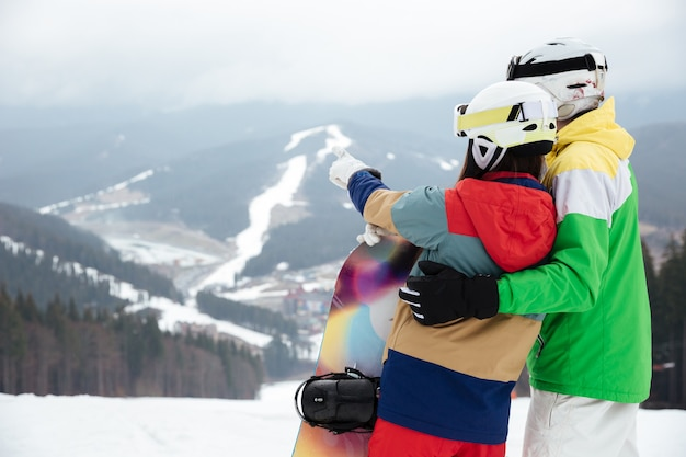Loving couple snowboarders on the slopes frosty winter day pointing