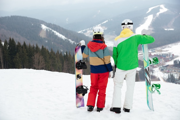 Loving couple snowboarders on the slopes frosty winter day