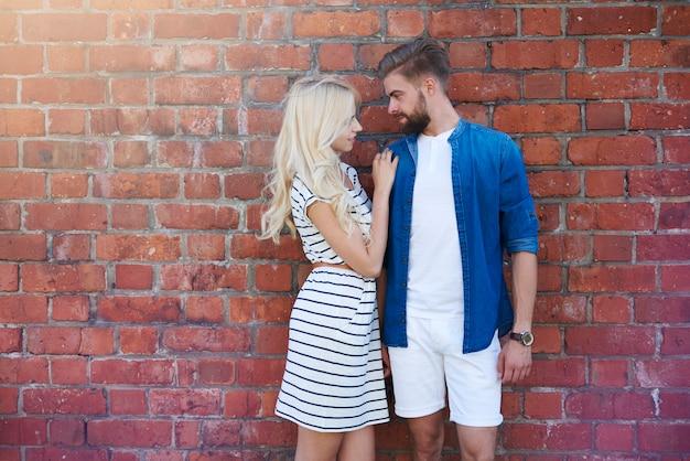 Влюбленная пара, стоящая перед кирпичной стеной