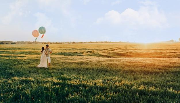 ヘリウム色のボールを持つフィールドに立っている愛情のあるカップル