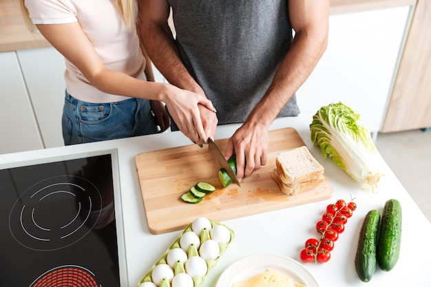 Loving couple standing at kitchen and cooking together