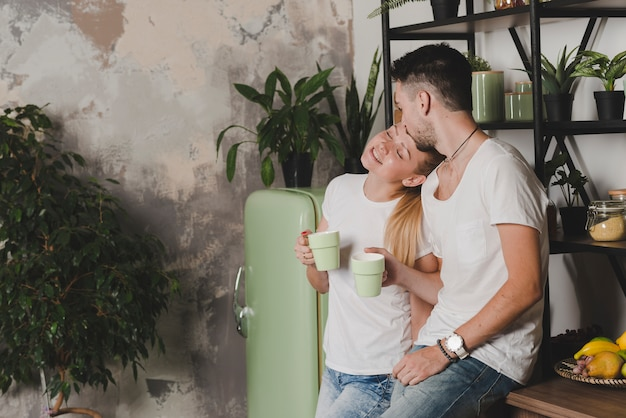 Loving couple standing in kitchen holding cup of coffee