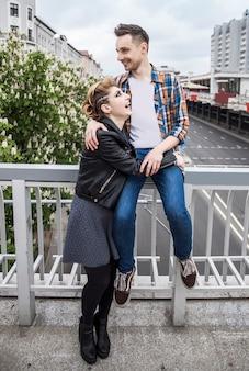 大都市の橋の上に立っている愛情のあるカップル