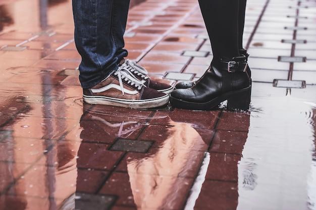 雨の秋の日に外に立っている愛情のあるカップル