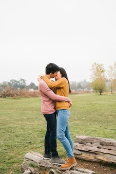 Loving couple standing on timber and kissing on meadow