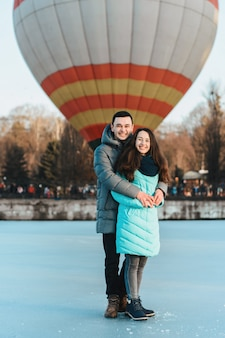 Loving couple stands on ice on valentine's day, behind the air ball.