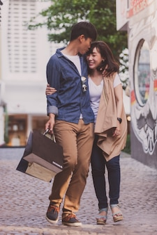 Loving couple strolling with shopping bags