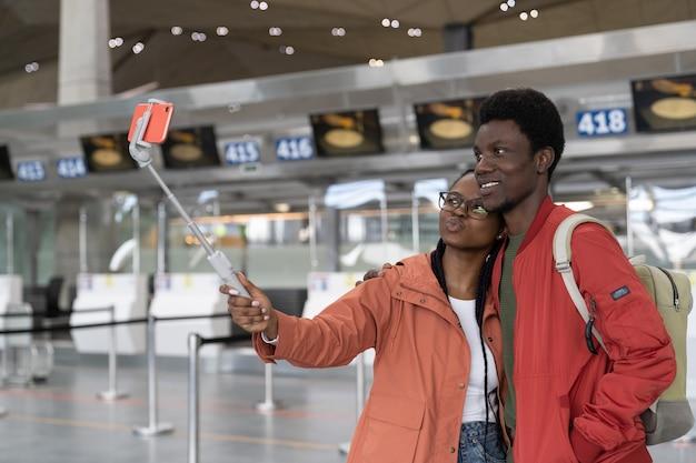 愛するカップルが空港で自分撮りをします