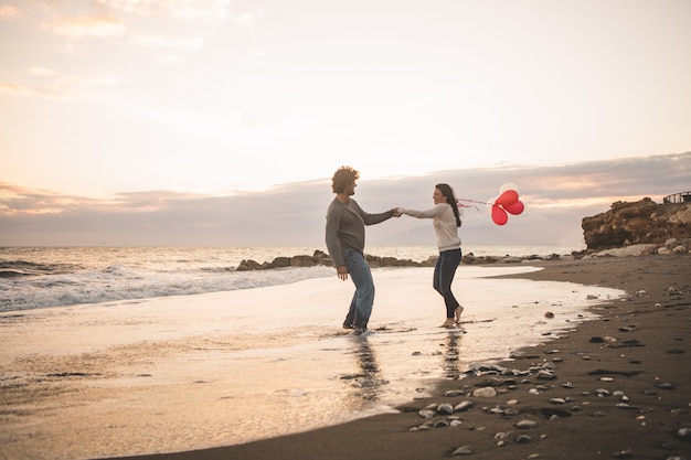 Loving couple throwing hands and her with balloons in hand
