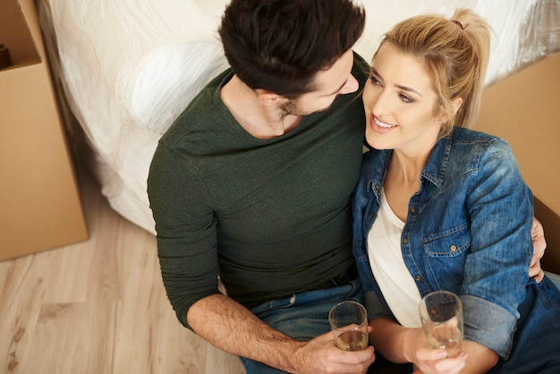 Loving couple toasting new apartment with champagne