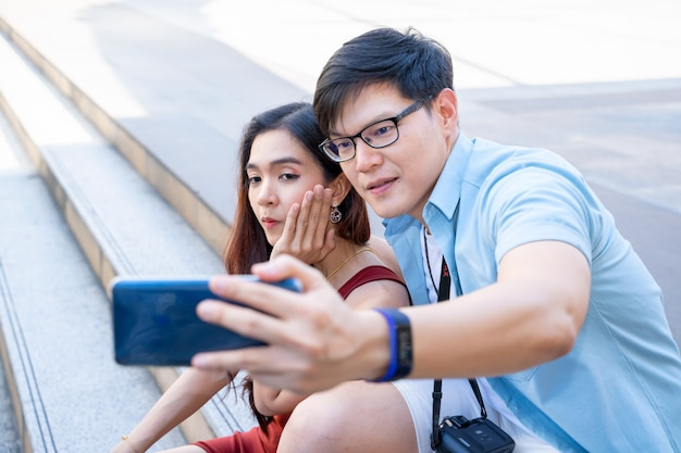 A loving couple tourist is taking a selfie on their smartphone in the city center,they ar holding each other,capturing bright moments.