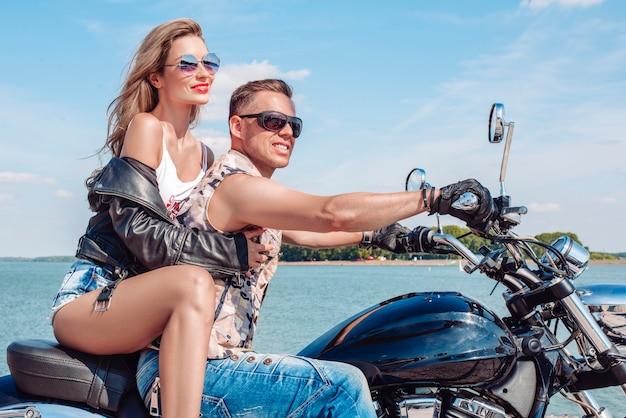 사랑하는 부부는 바다 근처에서 오토바이를 타고 여행합니다. 가족, 관광, 사랑 개념입니다. 혼합 매체