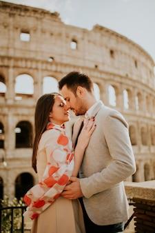 Loving couple visiting italian famous landmarks colosseum in rome, italy Premium Photo