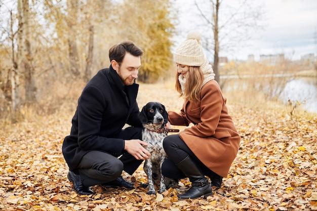 Loving couple walk through the autumn forest park with a spaniel dog