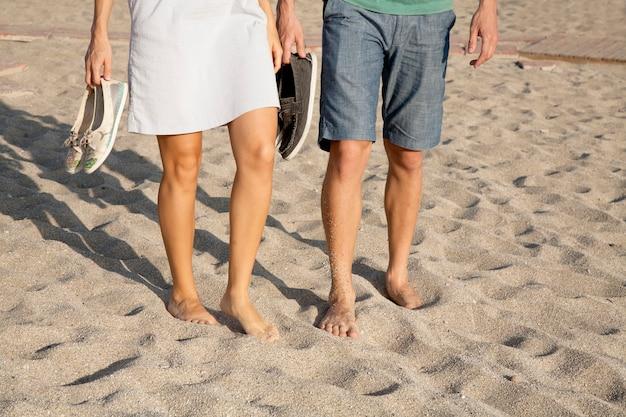 砂の上(ビーチ)を裸足で歩く愛情のあるカップルは、靴を手に持っています。